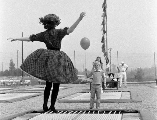 A black and white photo of a woman jumping on a trampoline, her skirt billowing, with a boy holding a balloon and watching her.