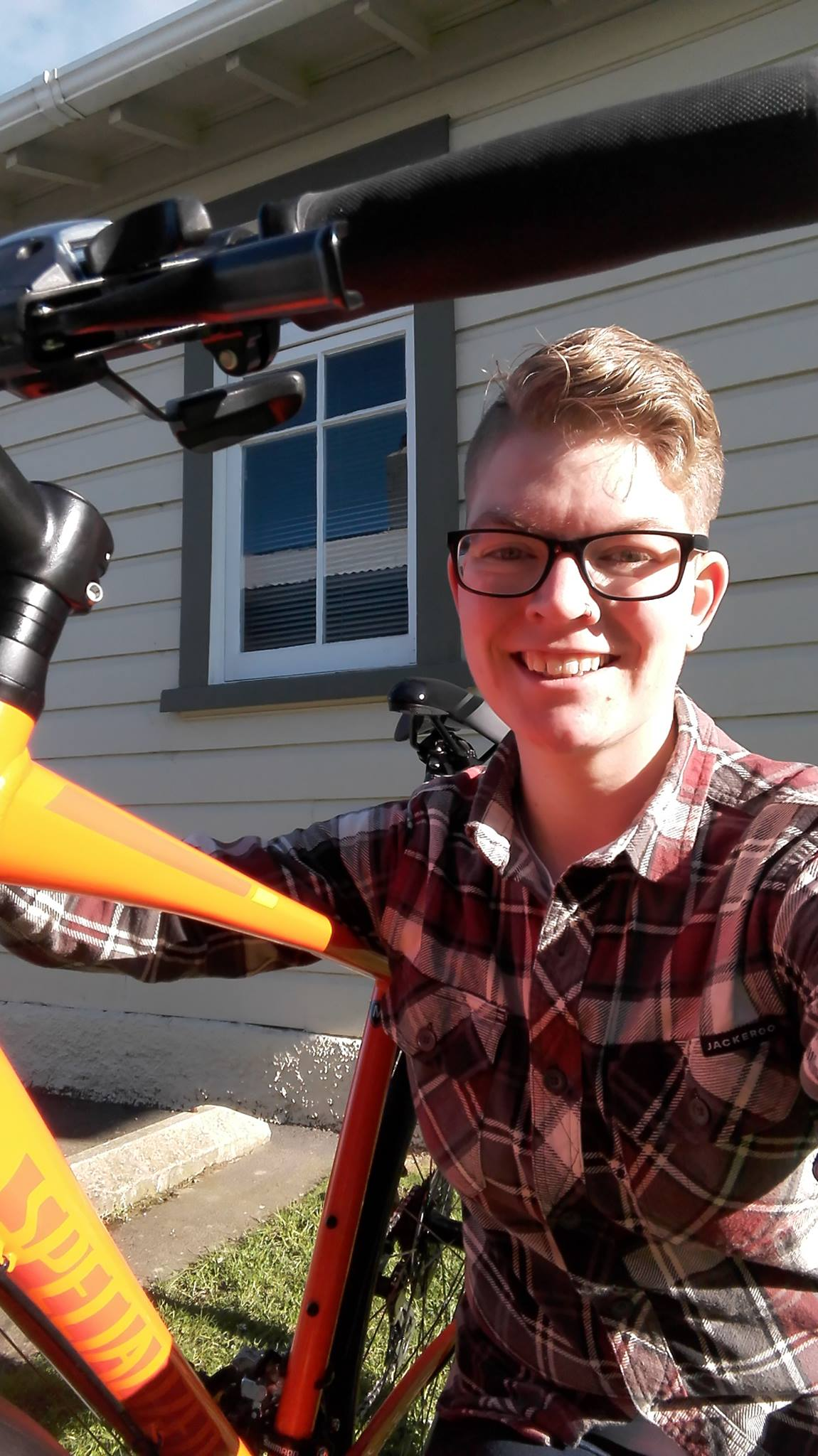 A 26-year old white woman with short blonde hair, wearing a red and grey plaid shirt and black glasses smiles while posing with her orange bicycle.