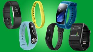 Six different fitness trackers--3 with black wrist bands, one light blue, one yellow, and one darker blue, all against a green background.