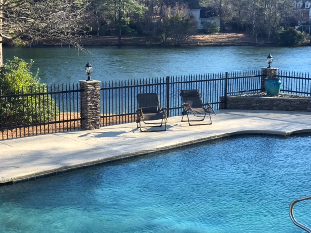 View of a blue-water pool, wit two reclining chairs on its patio, backed by a black wrought-iron fence, and lake in the background.