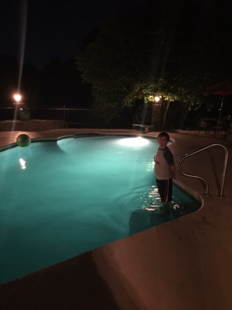 My sister's pool at night, with blue-green water and underwater lights, with my nephew Gray ready to take the plunge.