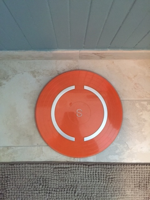 The Shapa scale, a bright orange disc on my bathroom floor with a white S in the middle.