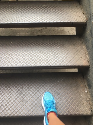 Three outside stairs (in Chicago) with a right foot in a robin blue running shoe and the bottom of a brown leg (Tracy's) on the lower step.