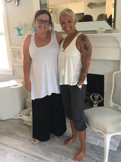 Kathy (left) and Tracy (right) in Nantucket, August 2017. Photo description: two women both in white sleeveless tops, Kathy in wide black pants, Tracy in grey capris. White fireplace mantel in background.