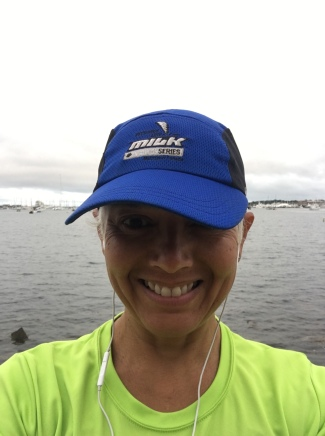 Image description: Headshot of Tracy, a woman of colour with short blond hair under a blue running cap, wearing white earbuds and a neon yellow t-shirt, Newport Harbor in the background, grey cloudy day.