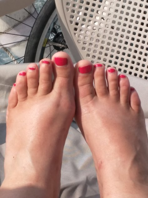 Tanned white feet with pink toenails resting on a white lawn chair