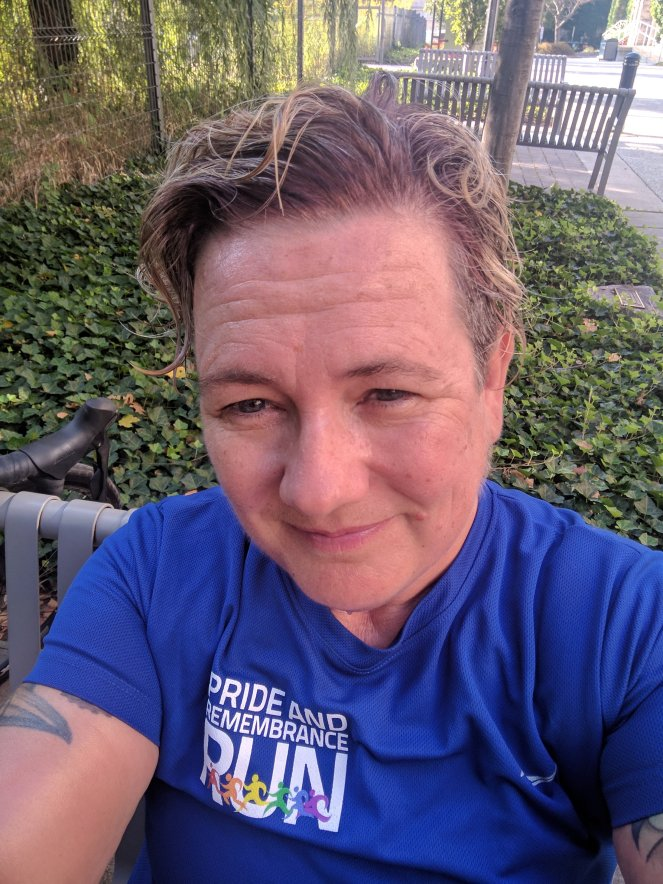 Sam in a blue pride run shirt hot and sweaty after a ride to work