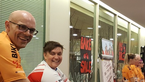 A bald man with glasses smiles at the camera looking over his shoulder. Natalie is next to him, spinning and smiling. The back drop is a bake sale table with food on it