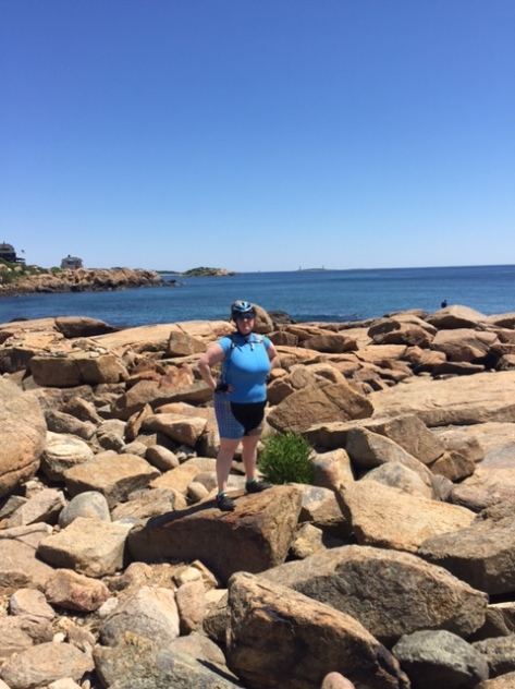 The author, posing confidently on rocks by the ocean on Massachusetts' north shore, despite the fact that she's wear cycling shoes with metal cleats and standing on a rock.