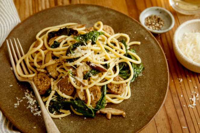 Spaghetti with black kale, shiitake mushrooms and diced sausage with a sprinkling of parmesan cheese, on a brown plate with fork.