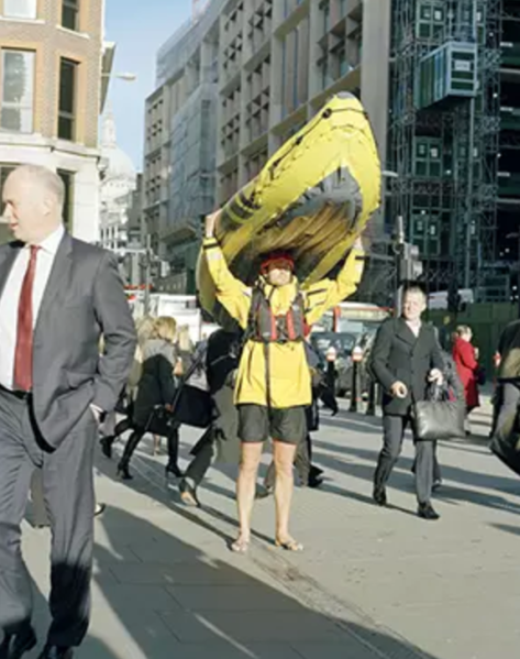 A man in shorts and a yellow coat and a life jacket, holding a yellow inflatable kayak over his head. He's standing in a crowd of commuting walkers downtown in a big city.