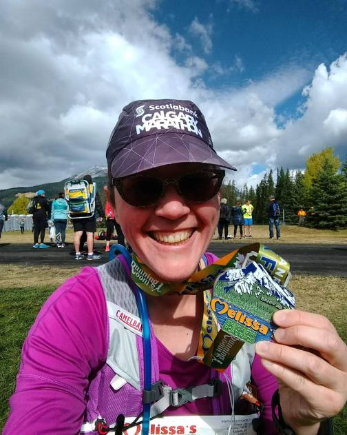 "Image description: Beaming in a ""Calgary Marathon"" blue ball cap, sunglasses, and a bright pink top, Heather holds up her finisher's medal, with an image of a snowy mountain, green slope, and water and the name, ""Melissa"" in orange lettering. Behind Heather is a small crowd, pine trees, and cloudy blue skies."