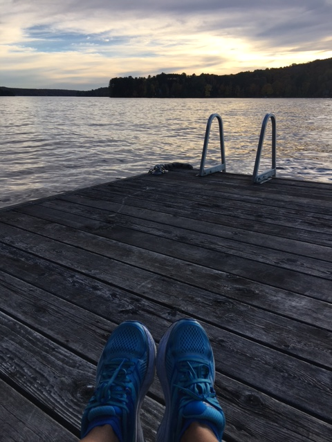 Image description: Tracy's feet in robin blue running shoes in the foreground, resting on a weathered wooden dock with a swim ladder going into the water, the lake, tree-lined shore, and cloudy skies with a hint of blue in the distance.