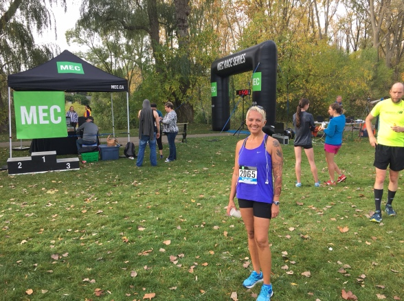 Image description: Tracy standing on grass in the foreground wearing black running shorts, a purple tank, bib number 2065, and robin blue shoes. She's smiling and holding an empty paper cup. Background is the MEC race arch and podium, a few people, and trees.