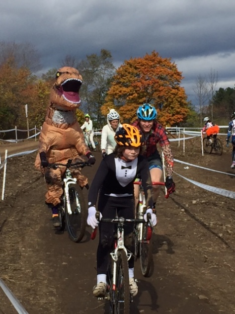 A group of costumed cyclists on a cyclocross course, with a T.Rex on the left.