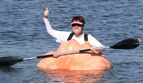 A woman in a large pumpkin with a kayak paddle in the water, smiling and giving a thumbs-up sign.