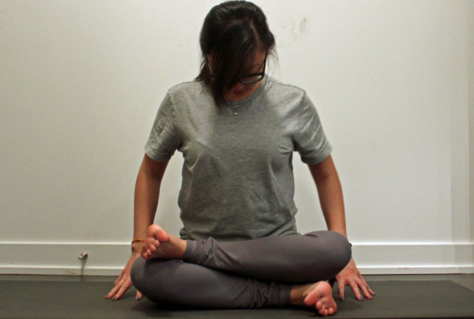 A woman seated on a yoga mat, right leg crossed in front, left leg on top of right leg, left ankle resting on right knee.