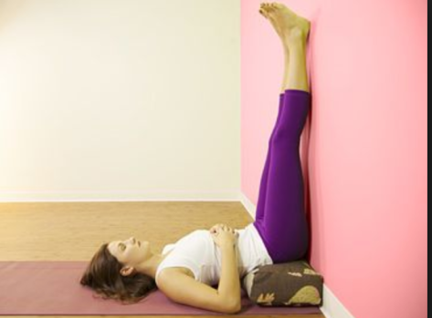 A woman in purple leggings and a white tank shirt lying on her back, buttocks on a bolster, legs up against a pink painted wall.