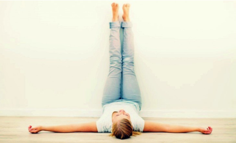 A woman lying on the floor, face up, with arms spread out in a T, and legs up and against a wall. Her butt is on a cushion against the wall.