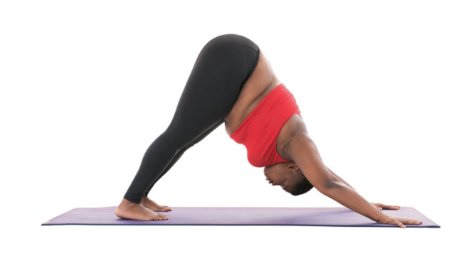 Yogi Jessamyn Stanley in downward dog, with legs on a mat, hips in the air, head down, and arms on the mat, in an inverted V.