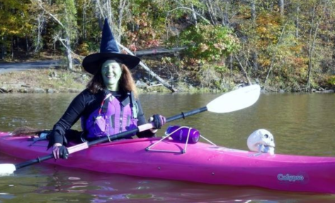 A woman in a purple kayak, dressed in a witch hat, green makeup, life vest (safety first!), with a skull on the bow.