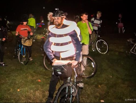 Boston Halloween bike ride participant, with illuminated tubes wrapped around his torso, standing by his bike at night.