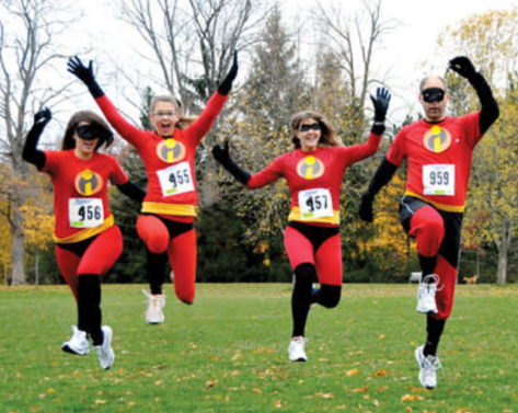 The family that runs together is incredible together. Family of four-- one man and three women-- dressed in Incredibles outfits with racing numbers.