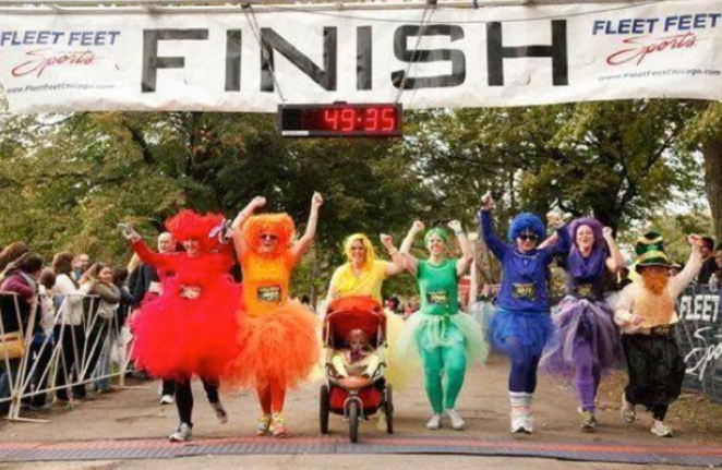 A merry band of multicolored costumed folks (red, orange, yellow, green, blue and purple, plus leprechaun) crossing the finish line at a road race.