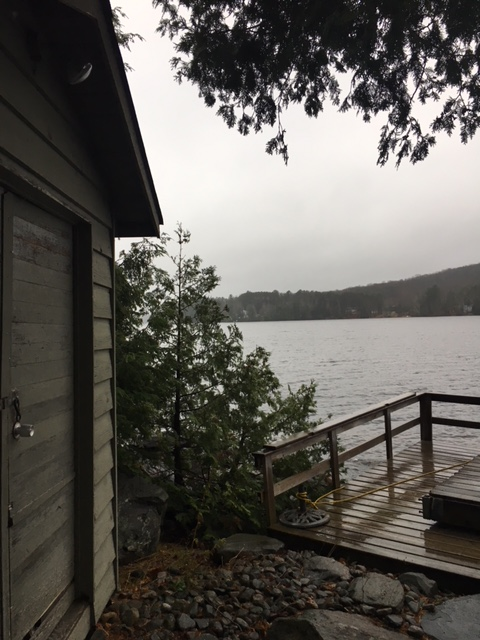 Image description: Lakeside scene of small grey sided bunkie (shed) with a padlock on the door, cedar, partial view of dock with lake and the other shore behind it, grey sky, stone covered ground in the foreground.