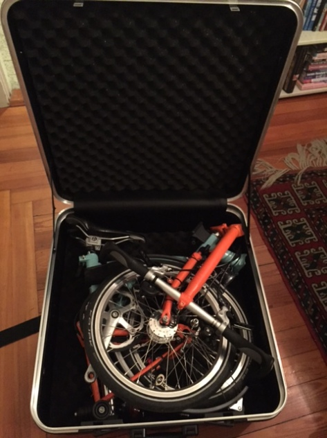 My open Brompton suitcase, with padding all around, and my folded bike snugly and comfortably resting inside.