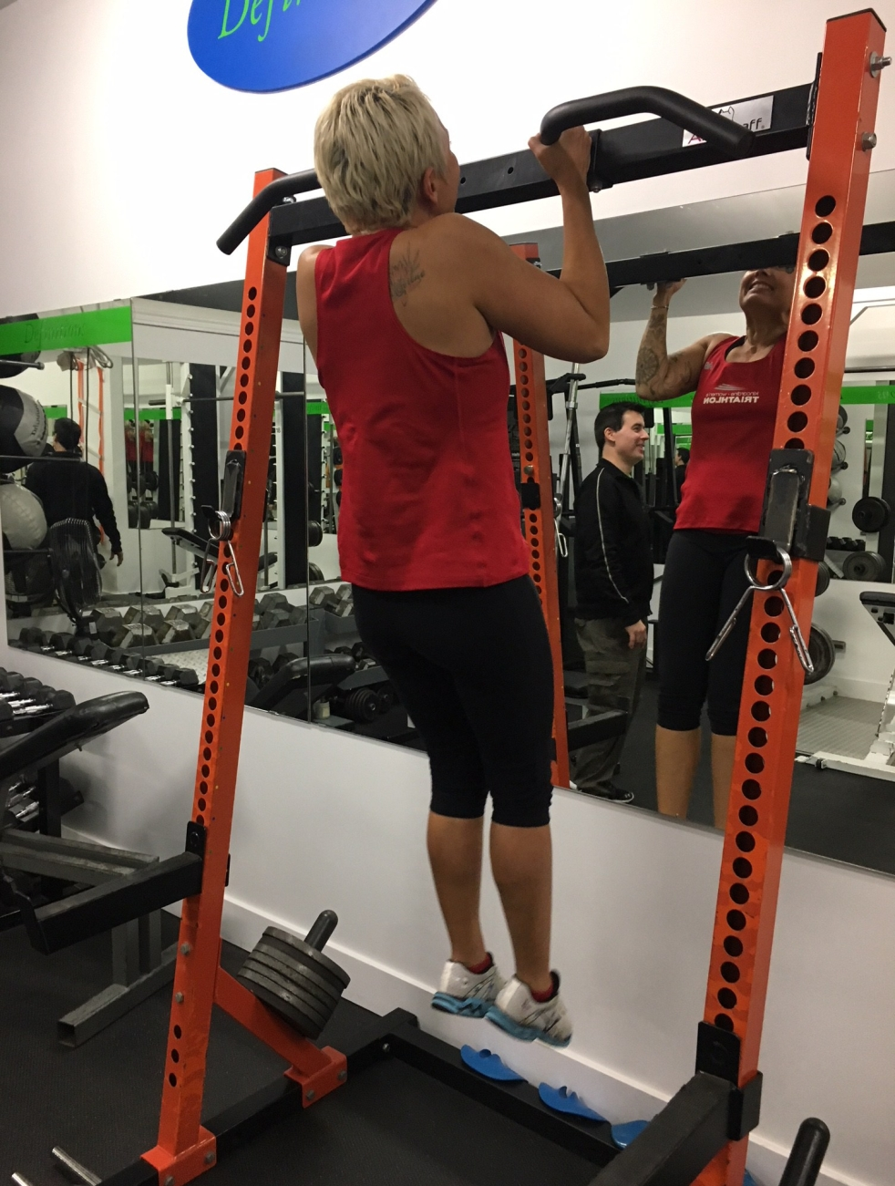 Image description: Tracy (short blond hair, red tank, black capris, white shoes, rear view facing mirror) doing a pull-up at Definitions Fitness, with Paul visible in the mirror looking on. Photo credit: Sam, who arrived for her workout right after Tracy's.