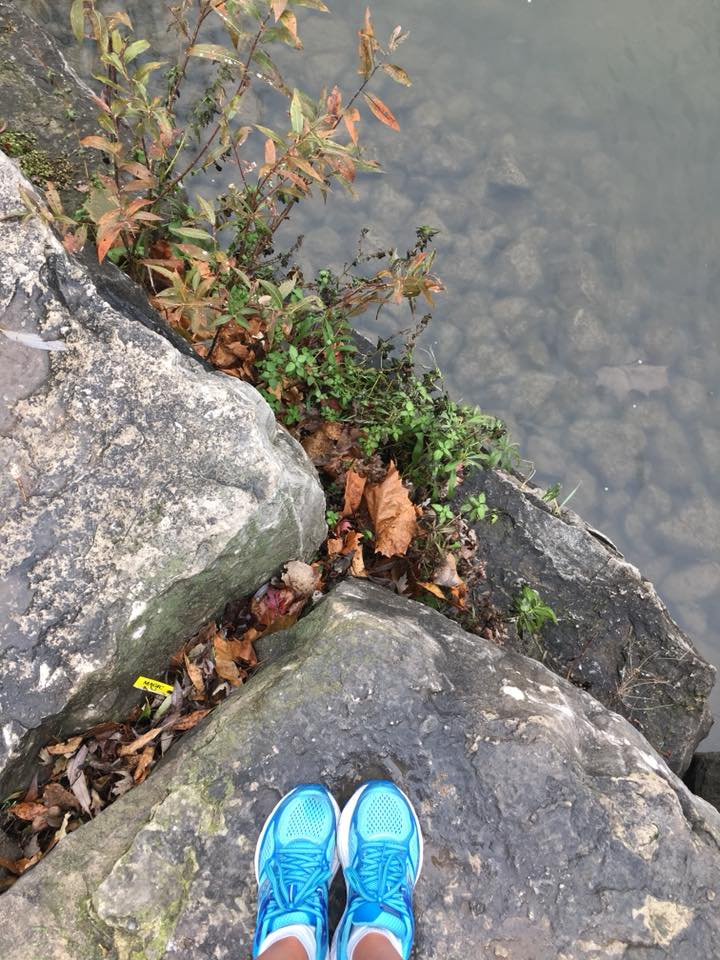 Image description: Tracy's two feet in robin blue running shoes on a stone slab beside the river, some dry leaves and greenery on the ground, the river cuts diagonally across the frame and you can see stones on the bottom through the clear water.
