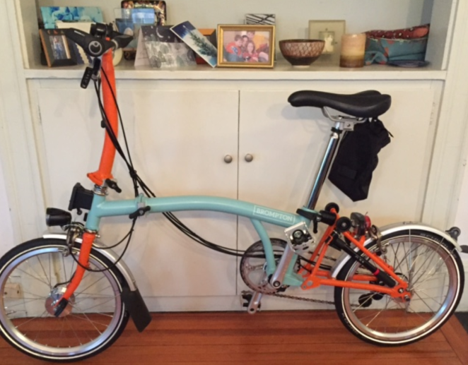 My Brompton foldable bike, in two colors: bright orange and celadon green.
