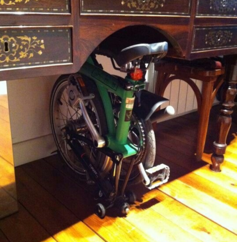 Not my Brompton, but a lovely cut-out nook under a wood sideboard for a nice green Brompton to take a load off and rest.