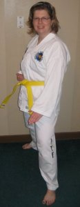 The author wearing her white martial arts uniform with a yellow belt around her waist. She is smiling, standing slightly sideways, with her left hand held flat at thigh height.