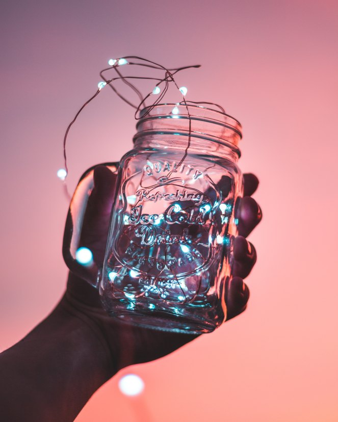 Against a pink background a hand holding a mason jar with fairy lights