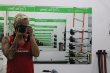"Image description: Tracy (short blond hair, red tank, tattooed arm, holding her camera and taking a picture in the mirror, producing the infinity effect. Mirror has a green banner a the top that says ""Definitions."""