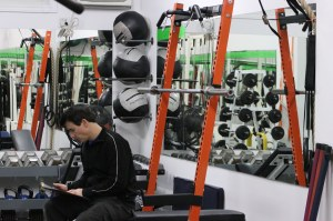 Image description: Paul (a thirty-something man with short dark hair, wearing a black workout jacket with a white strip on the arm and black pants) sitting on a bench in front of the orange squat rack, looking at the workout notes. Workout equipment (dumbbells on racks, medicine balls) and mirrors are in the background.