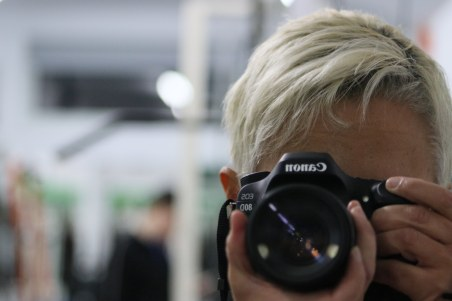 Image description: Tracy (short blond hair) in the foreground holding the Canon D80, taking a picture into the mirror. In the blurred background is Paul, mirrors, workout equipment.
