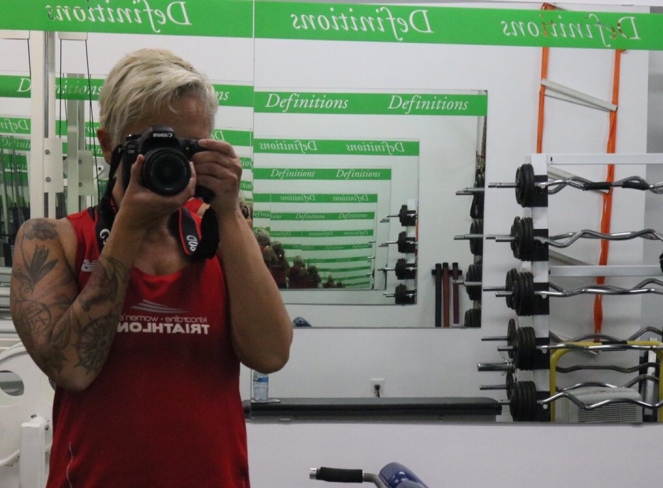 """Image description: Tracy with short blond hair, tattooed arm and a red tank is looking through the viewfinder of a camera, facing into a mirror, with an infinity affect. """"Definitions"""" is in a green banner on the mirror."""