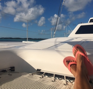 Blue sky with a few clouds, mesh of the corner of a trampoline on a catamaran, with a person reclining on it, feet with pink flip flops visible in the lower right corner.