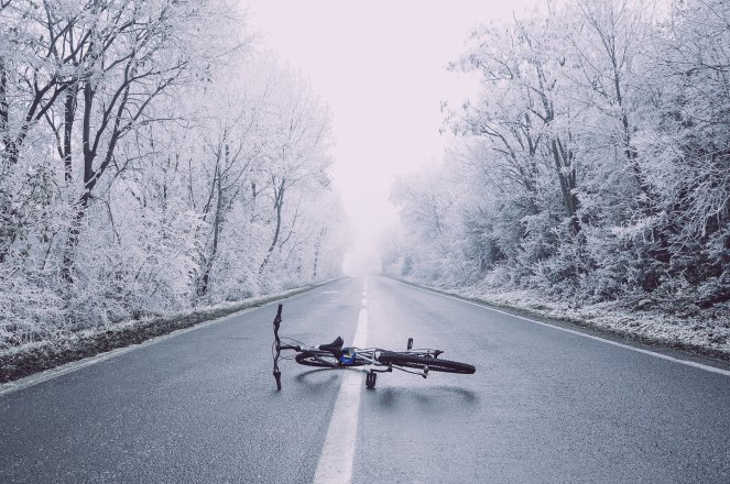 Photo by Petar Petkovski on Unsplash, image description: a road surrounded by snow trees with a bike laying down on the center line