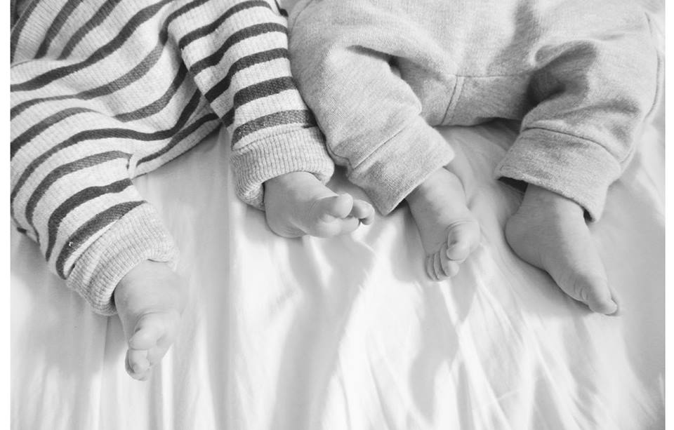 Image description: black and white photo of baby twin feet in rompers