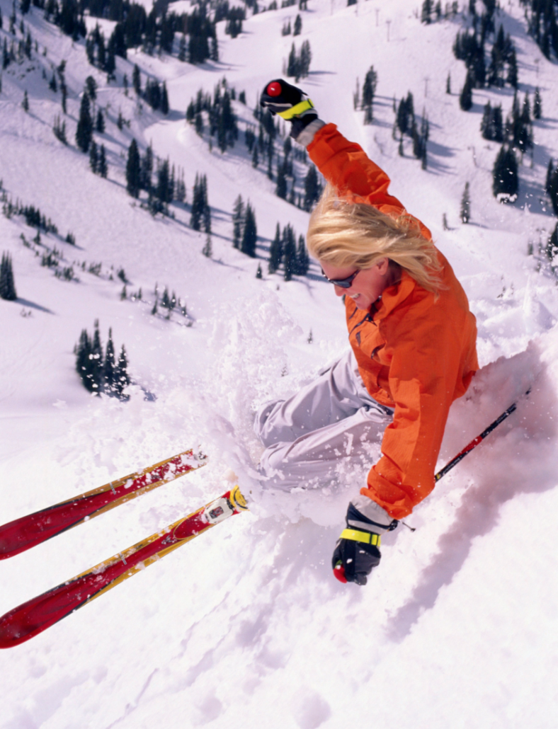 A woman in an orange ski jacket carving  turn down the side of a mountain.