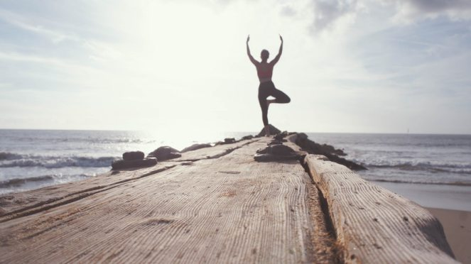 Silhouette of a person doing yoga at the end of a pier