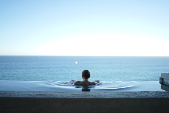 Female figure alone in an infinity pool looks towards the ocean in the distance