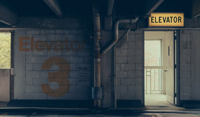 "Photo of a parking garage elevator with a yellow ""elevator"" sign"