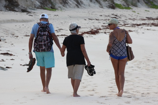Image description: Rear shot of Tracy's parents walking hand in hand on a white sandy beach, her Dad on the left wearing light blue shorts, a blue t-shirt, a plaid back page and a white cap, and her Mum on the right, wearing beige shorts and a long black t-shirt and black sun visor. Both are holding their shoes. Tracy walks along side in a blue boy-cut swimsuit bottom, a tank top, a faded khaki ball cap and sunglasses, carrying a fabric shoulder bag. She's turning her head towards her parents, and smiling.