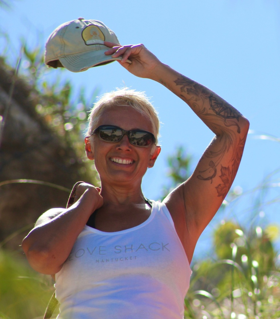 "Image description: Upper body shot of Tracy, short blond hair, sunglasses, and smiling, wearing a white tank that says ""Love Shack Nantucket"" on the front and holding a faded ball cap over her head in her left hand. Left arm is tattooed. Background is blue sky, grassy and sand."
