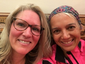 Head shot of two smiling women (Julie left and Tracy right). Julie has long light hair and is wearing glasses. Tracy is wearing a multi-coloured headband and a neon pink running jacket.